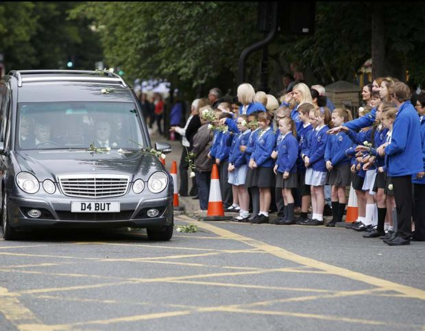 School children and teachers throw flowers on to the hearse carrying murdered Member of Parliament Jo Cox's as her funeral cortege will passes through Heckmondwike in northern Britain
