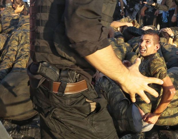 A police officer talks with the soldiers involved in the coup attempt after they surrendered