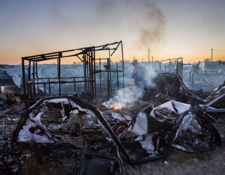 A police officer investigates a small fire amidst the devastation inside the Calais Jungle, Calais, France. 27 October 2016.