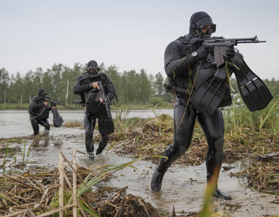 Combat divers are armed with night vision goggles and underwater submachine guns