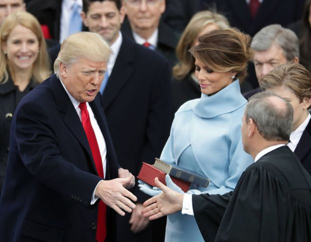 Supreme Court Justice John Roberts (R) congratulates U.S. President Donald Trump (L) after administering the oath of office as his wife Melania Trump holds the Bible, on the West Front of the U.S. Capitol on January 20, 2017 in Washington, DC