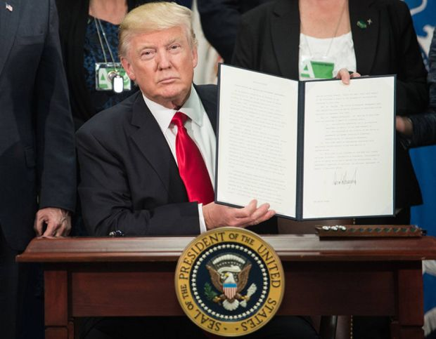 US President Donald Trump signs an executive order to start the Mexico border wall project at the Department of Homeland Security facility