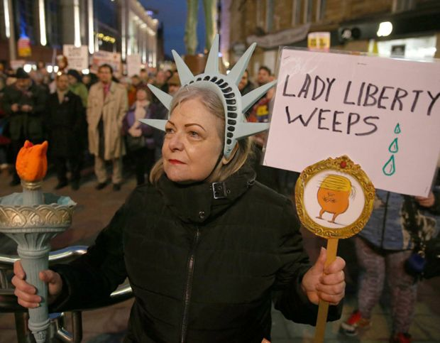 A woman dress as the Statue of Liberty during a protest in Glasgow against US President Donald Trump's controversial travel ban on refugees and people from seven mainly-Muslim countries