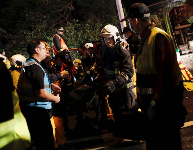 Rescuers remove a body from a crashed bus in Taipei