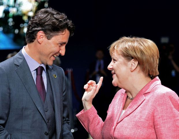 German Chancellor Angela Merkel and Canadian Prime Minister Justin Trudeau chat prior to the meeting of the NATO-Ukraine Commission