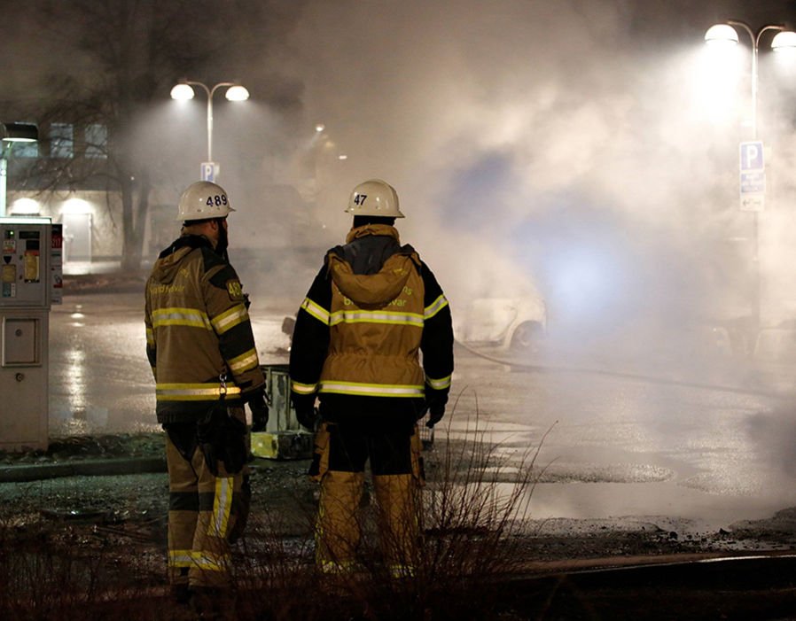 Firefighters are seen as several cars were set on fire during a riot, according to local media, in Rinkeby suburb, outside Stockholm