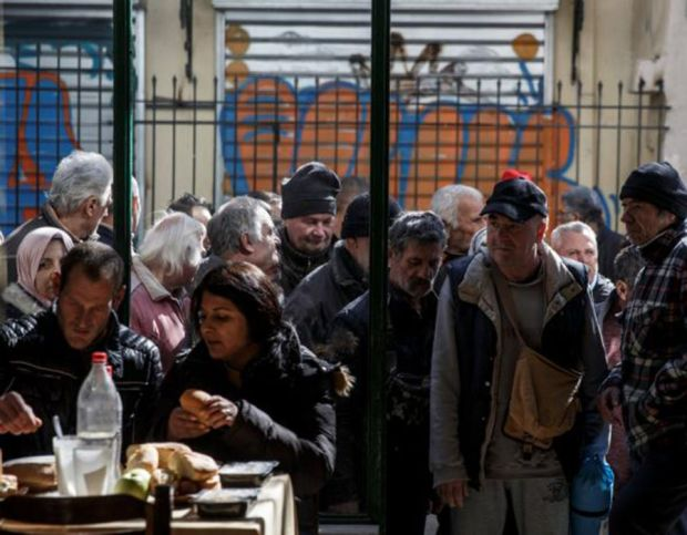 People line up as they wait to enter a soup kitchen run by the Orthodox church in Athens, Greece
