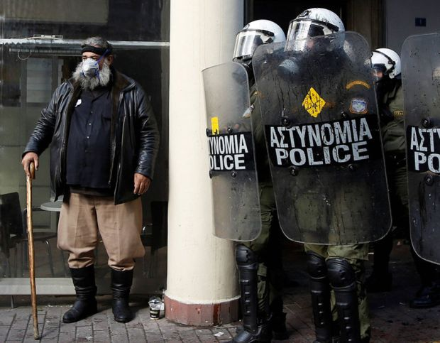 A farmer from the island of Crete stands next to riot police during clashes outside the Agriculture Ministry in Athens