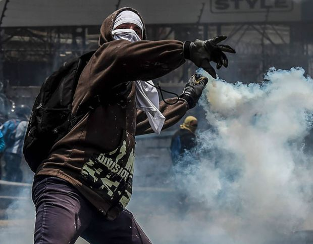 A demonstrator protesting against President Nicolas Maduro's government throws back a tear gas grenade at riot police in Caracas