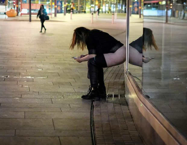 A women rests against a shop front in Liverpool