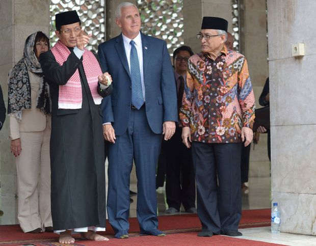 Nasarudin Umar (L) and Muhammad Muzammil Basyuni (R) show the Istiqlal grand mosque to US Vice President Mike Pence in Jakarta