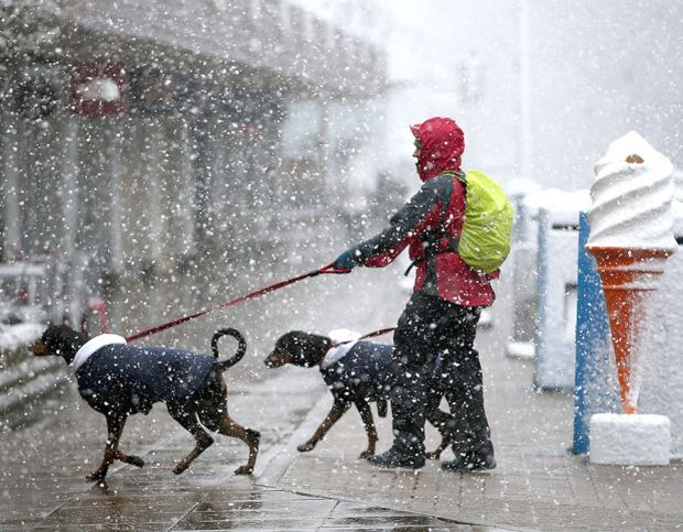 People walk through a snow shower along Grampian Road in Aviemore, Scotland,as the blast of Arctic weather that has brought snow to northern Scotland begins to move south
