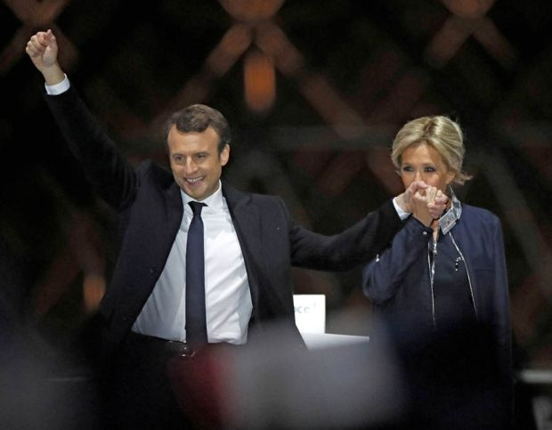 Brigitte Trogneux kisses her husband's hand as he is named President of France