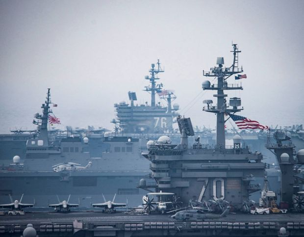 US and Japanese flags are visible on the USS Carl Vinson and USS Ronald Reagan