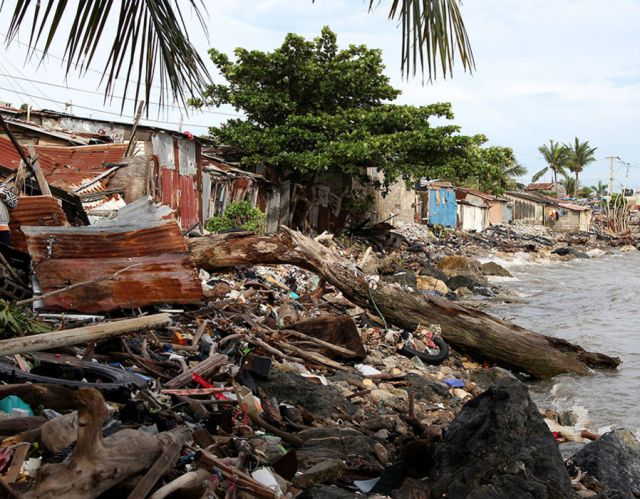 Debris is piled up next to the houses on the seashore in the aftermath of Hurricane Irma in Puerto Plata