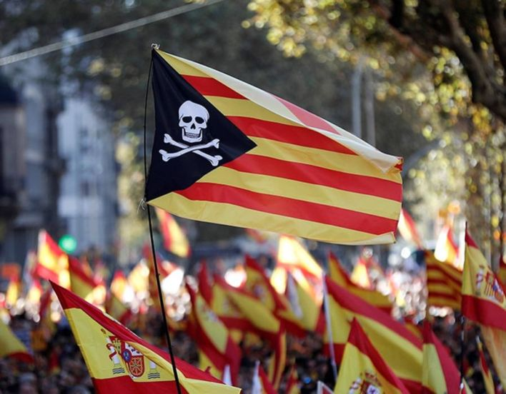 A protester waves a pirate-shaped collage of a Catalan Flag during a pro-unity demonstration at Passeig de Gracia in Barcelona