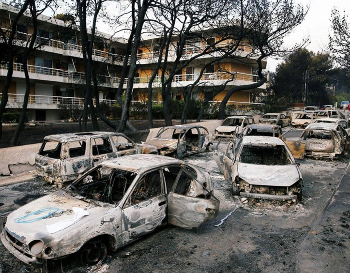 Burned cars are seen following a wildfire at the village of Mati, near Athens