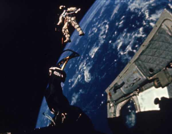 Astronaut Edward White walking in space tethered to