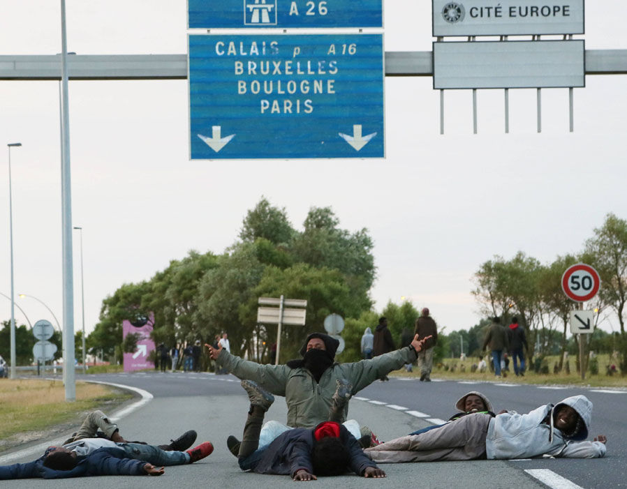 Migrants sit and lay in the road in Calais