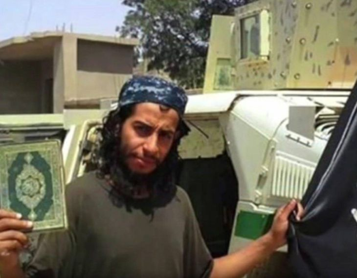 Abdelhamid Abaaoud posing with a Koran and the ISIS flag at an undisclosed location