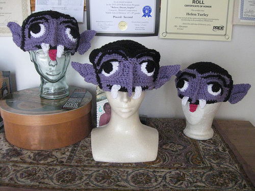 Three crocheted Count von Count hats