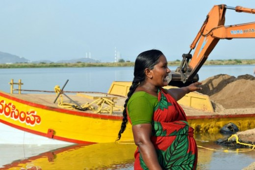At dawn women miners gather at allocated sites along riverbanks in India's coastal Andhra Pradesh state to oversee the process of dredging, loading and shipping sand. Credit: Stella Paul/IPS