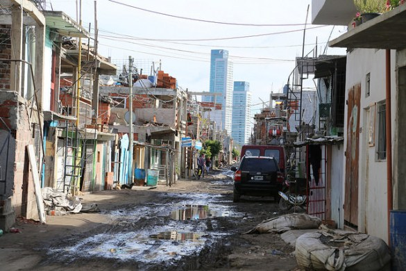 A muddy unpaved street in Villa 31, a shantytown in the heart of Buenos Aires that is home to some 60,000 people. In the background are seen buildings in one of the poshest districts of the capital, just 200 metres away. Credit: Fabiana Frayssinet/IPS
