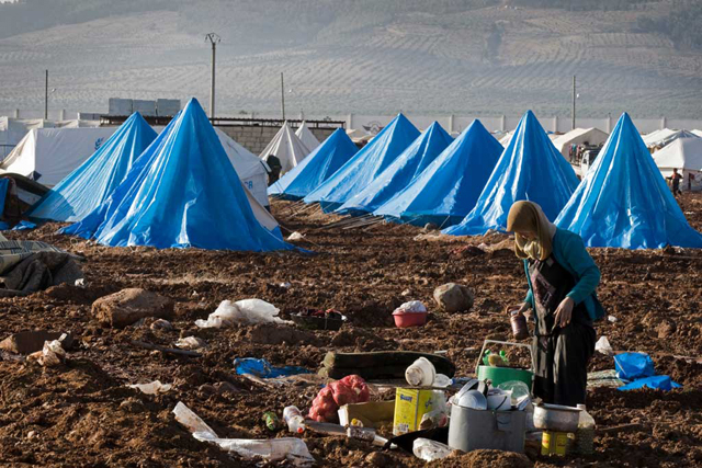 A woman prepares a meal at a makeshift outdoor cooking area, atop the muddy grounds of the Bab Al Salame camp for IDPs, near the border with Turkey in Aleppo Governorate, Syria (January 2014). Photo credit: UNOCHA