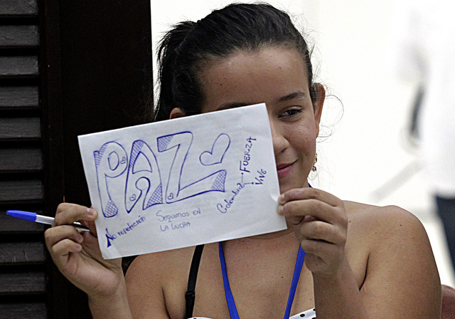 Erika Paola Jaimes, a survivor of Colombia's armed conflict, holds a sign about peace during a trip to Havana to participate in the peace talks between the government and the FARC rebels, which led to a peace deal signed Jun. 23 in the Cuban capital. Credit: Jorge Luis Baños/IPS