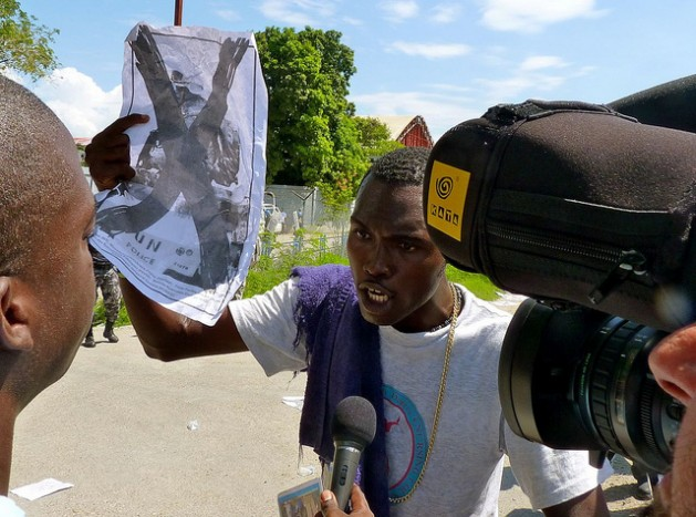 A demonstrator holds up an anti-U.N. poster during a protest outside a UN base in Port-au-Prince, Haiti. Credit: Ansel Herz/IPS