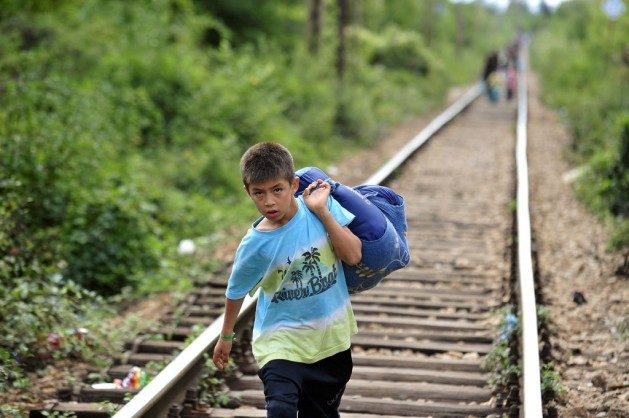 A boy carrying his belongings in a large cloth bag over his shoulder is among people walking on railway tracks to cross from the Former Yugoslav Republic of Macedonia into Serbia. Photo: UNICEF/NYHQ2015-2203/Georgiev