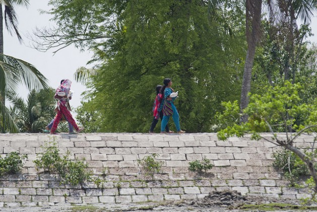Girls walk across an embankment in the Satkhira district of Bangladesh. Credit: Rafiqul Islam/IPS