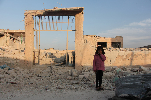 A seven-year-old child stands in front of her damaged school in Idleb, Syria. October 2016. Credit: UNICEF