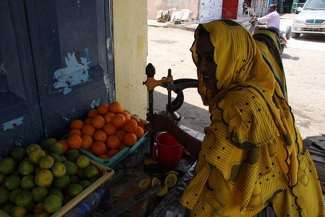 While Djibouti's maritime commerce and government's ambitions continue apace, for the average local Djiboutian everyday life remains unaffected by dreams of an African Dubai. Here a lady makes fresh juices on the street to slake the thirsts of sun-blasted pedestrians in Djibouti city's African quarter. Credit: James Jeffrey/IPS