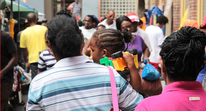 A Child Holds A Toy As He Is Carried By A Woman In Middle Street Kingstown On Christmas Eve 2013. (Iwn Photo)