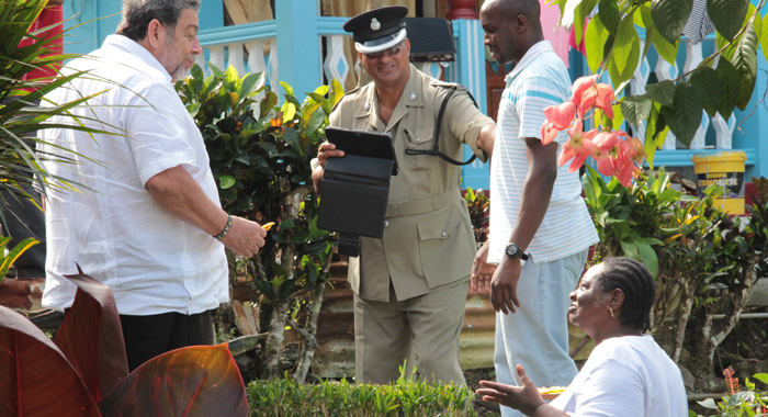 A Police Officer Nudges A Member Of Prime Minister Dr. Ralph Gonsavles' Security Detail Out Of The Way As He Attempts To Take A Photograph Of Gonsalves, Right, Eating Fried Plantain From A Resident Of North Leeward During A Tour Of Disaster-Affected Areas There On Dec. 27, 2013. Gonsalves Is On A List Of The Caribbean's Most Interesting Persons For 2013. (Iwn Photo)
