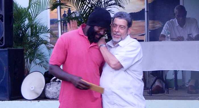 Prime Minister Dr. Ralph Gonsalves Makes The Presentation To A Recipient In Colonairie On Friday. (Photo: Nbc Radio/Facebook)
