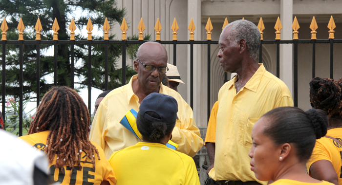 Ndp President Arnhim Eustace And Other Protesters Outside The Financial Complex On Monday. (Iwn Photo)