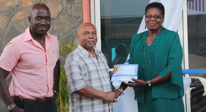 Sports Minister Cecil &Quot;Ces&Quot; Mckie, Centre, Presents The Award To Honouree Genita Lewis, Right, As Kevin Dickson, Chair Of Coreas Pharmacy Council Looks On. (Iwn Photo)