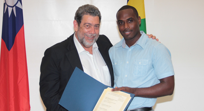 Clint Lewis, The First Vincentian To Be Awarded A Scholarship To Read For A Phd In Taiwan, Receives His Certificate From Prime Minister Gonsalves. (Iwn Photo)