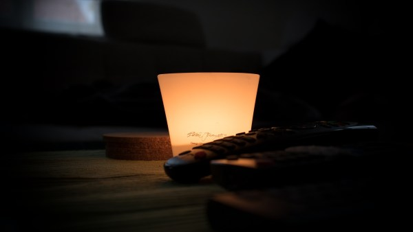 A candle burns in a glass jar on a table in a dark room