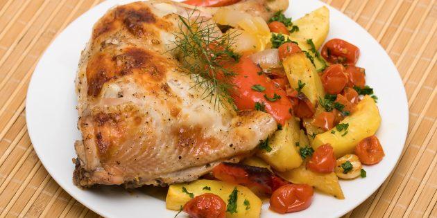 Poutres poulets avec pommes de terre et tomates dans le four