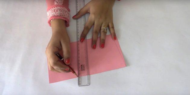 Falten Sie ein Blatt rosa Papier in der Hälfte