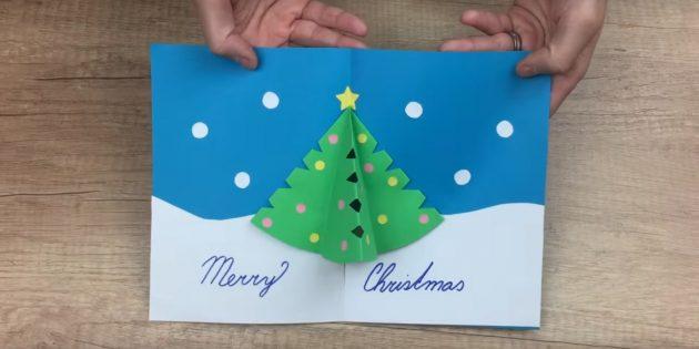 کارت پستال سال نو با دست خود را با یک درخت کریسمس بزرگ در داخل