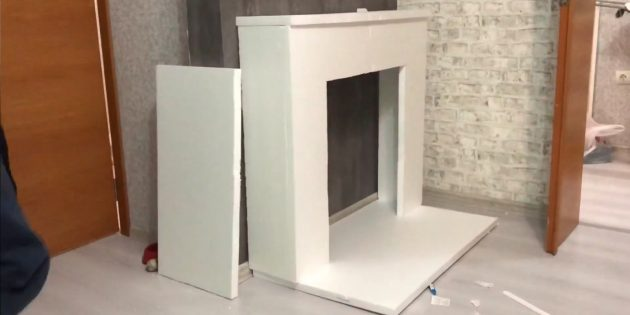 Decorative fireplace with your own hands: Install the fireplace on the base and stick it
