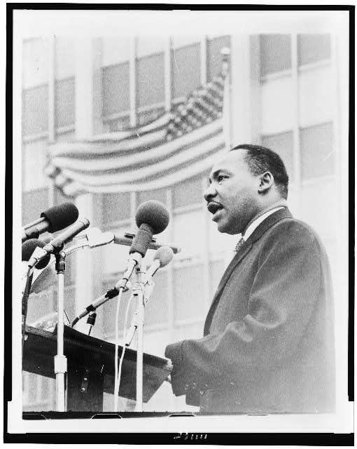 [Martin Luther King, Jr., half-length portrait, facing left, speaking at microphones, during anti-war demonstration, New York City]