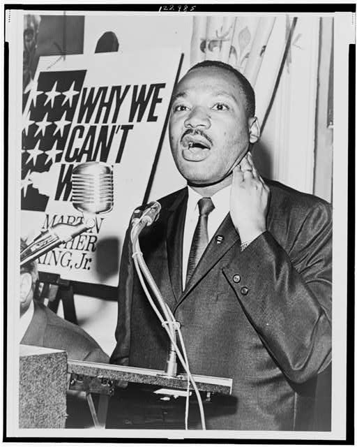 [Martin Luther King, Jr., three-quarter-length portrait, standing, facing front, at a press conference]