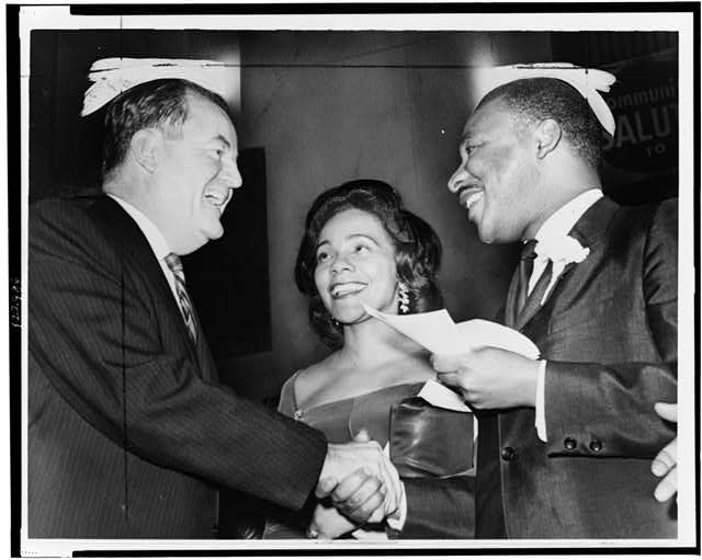 [Vice President-elect Hubert Humphrey shaking hands with Dr. King, as Mrs. King looks on, at a rally at Harlem's 369th Regiment Armory]