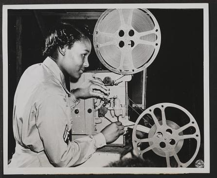 Black and white ca. 1940-1950 image of a young black woman threading film into an old-fashioned projector.