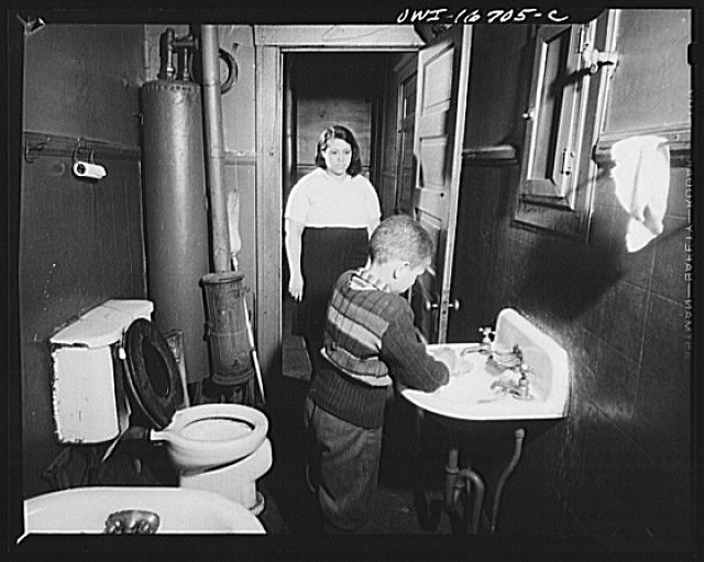 Detroit, Michigan. Interior of a bathroom, with a Negro boy washing his hands. These are conditions under which families originally lived before moving to the Sojourner Truth housing project